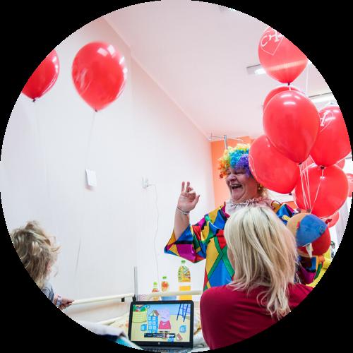 Zdjęcie przedstawiające osobę przebraną za klauna podczas wizyty na dziecięcym oddziale szpitalnym