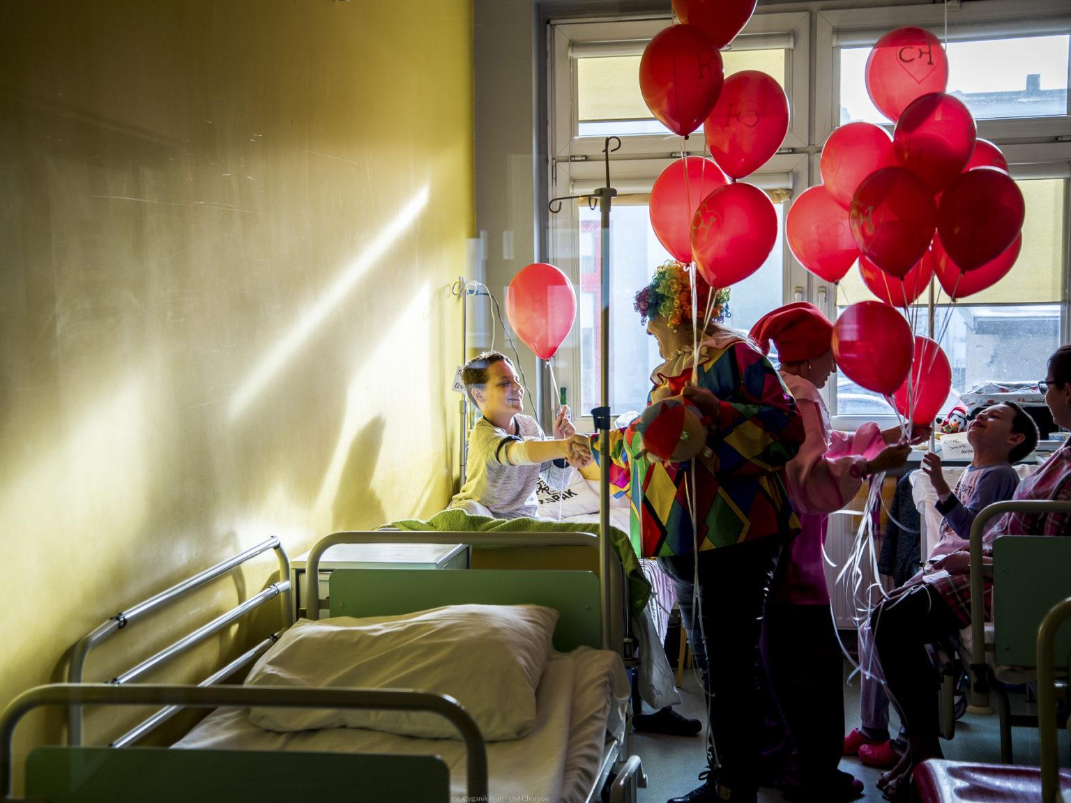Zdjęcie przedstawiające seniorki w strojach klauna wręczające balony dzieciom - pacjentom szpitala
