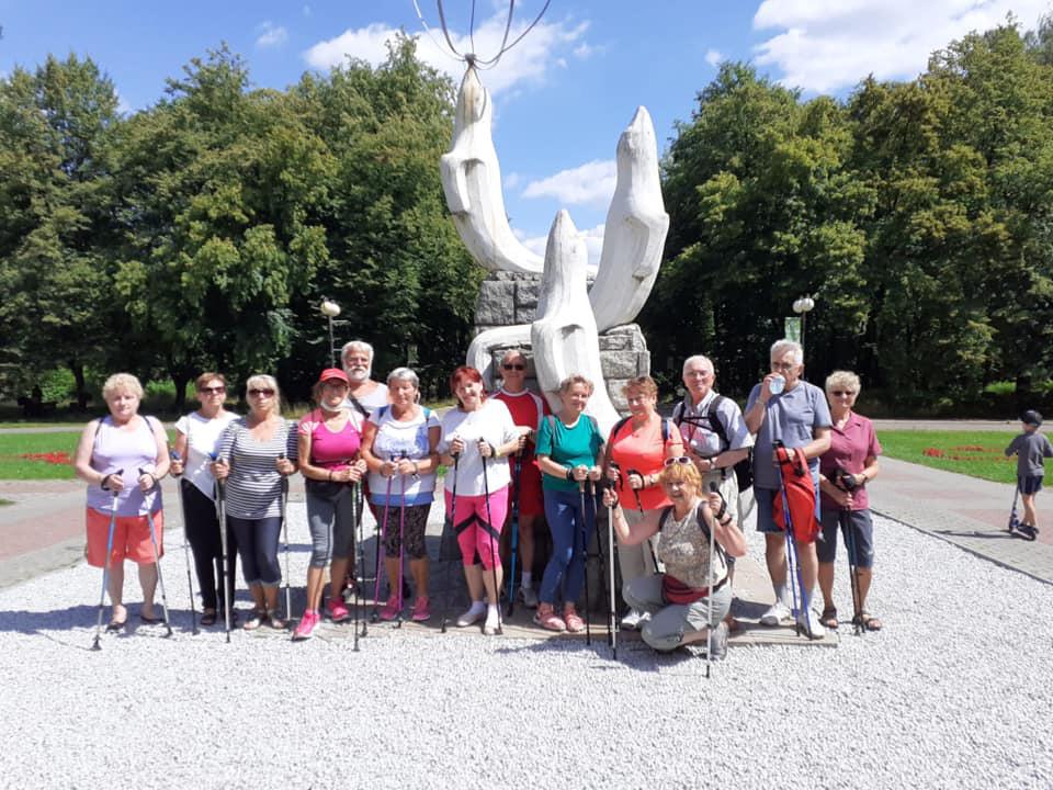 Zdjęcie przedstawiające grupę seniorów z kijkami do nordic walking