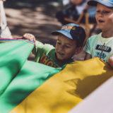 Zdjęcie przedstawiające dwóch chłopców podczas zabawy z kolorową chustą