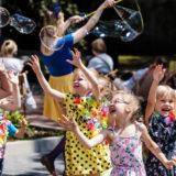 Zdjęcie przedstawiające dzieci próbujące złapać bańki mydlane