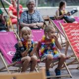 Zdjęcie przedstawia dzieci siedzące na leżakach i spożywające lody