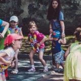 Zdjęcie przedstawiające grupę osób - dorosłych oraz dzieci - podczas zabawy