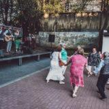Zdjęcie przedstawiające zespół Larmodzieje podczas występu oraz tańczących pod sceną seniorów