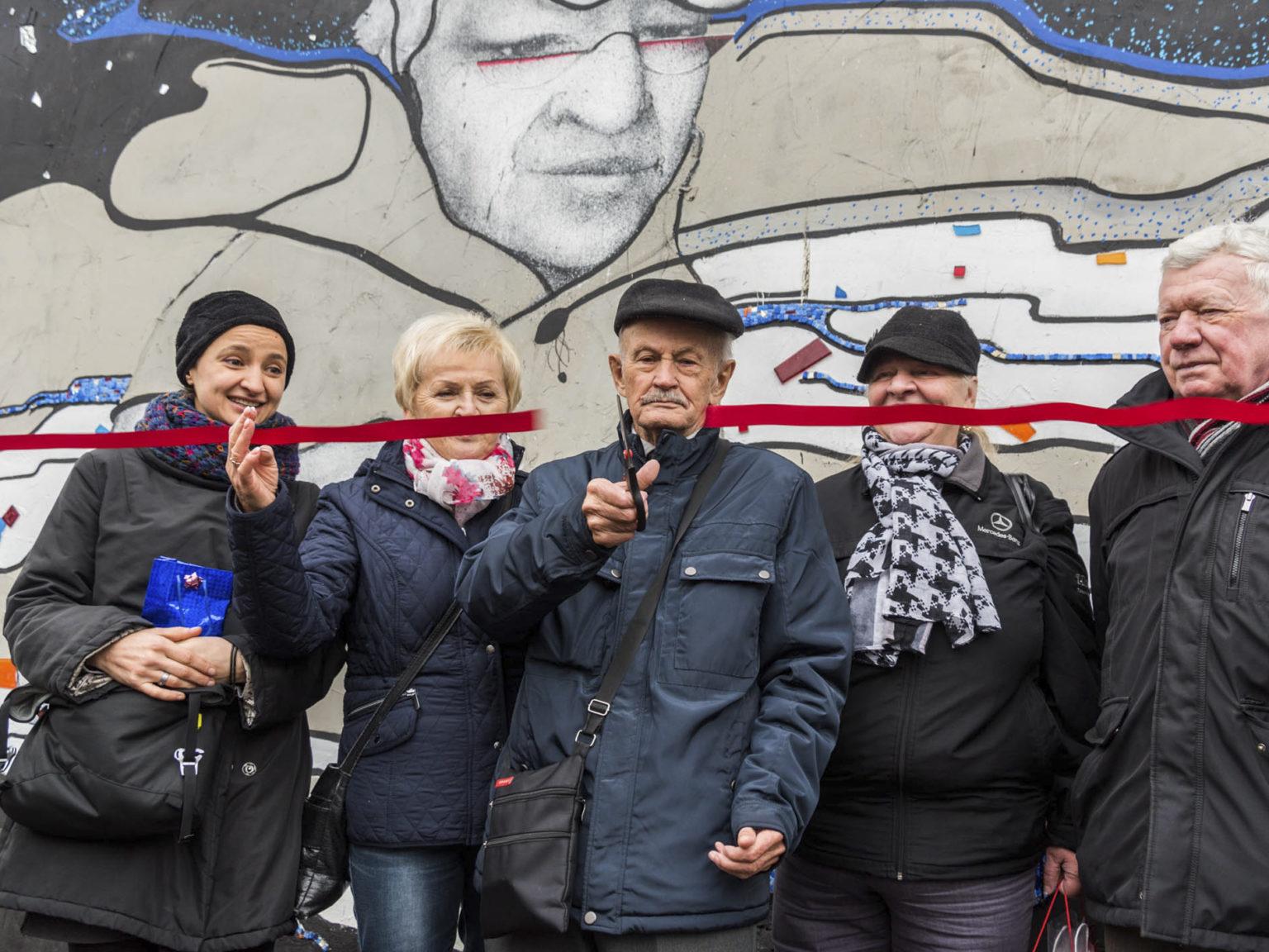 Zdjęcie przedstawiające seniorów przecinających wstęgę przed międzypokoleniowym muralem