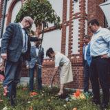 Zdjęcie przedstawiające Marcina Michalika, zastępcę prezydenta Chorzowa, chorzowskich radnych oraz Martę Jakubczyk, dyrektor Centrum Integracji Międzypokoleniowej, podczas wkopywania drzewa pod siedzibą CIM