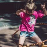 Zdjęcie przedstawiające dziewczynkę podczas zabawy hula-hop